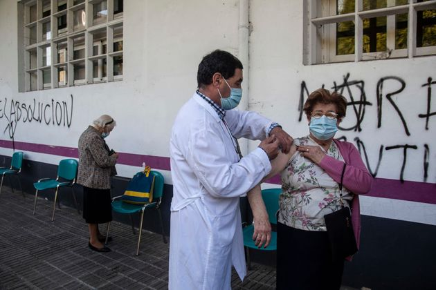 Un sanitario vacuna a una mujer mayor en Noreña