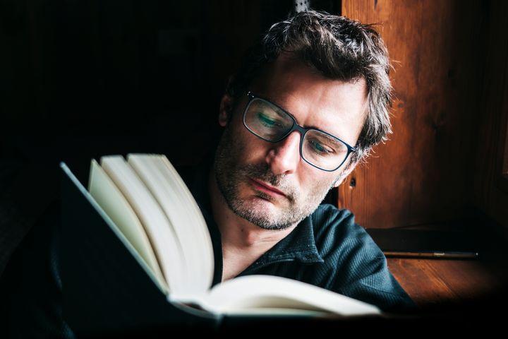 Una hombre leyendo un libro.