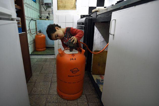Un niño con una bombona de butano en su casa de