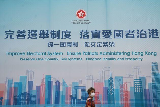 Μία γυναίκα περνάει μπροστά από μία διαφήμιση που προωθεί τις εκλογικές μεταρρυθμίσεις του Χονγκ Κονγκ, μετά την έγκριση του κινεζικού κοινοβουλίου για ένα νέο σχέδιο μεταρρύθμισης του εκλογικού συστήματος,