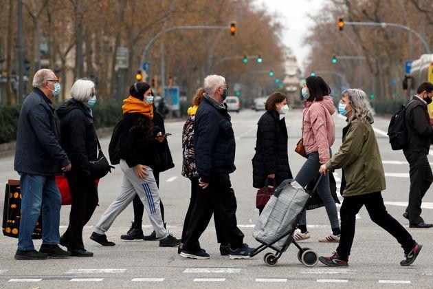 Ciudadanos con mascarilla, caminando por el centro de