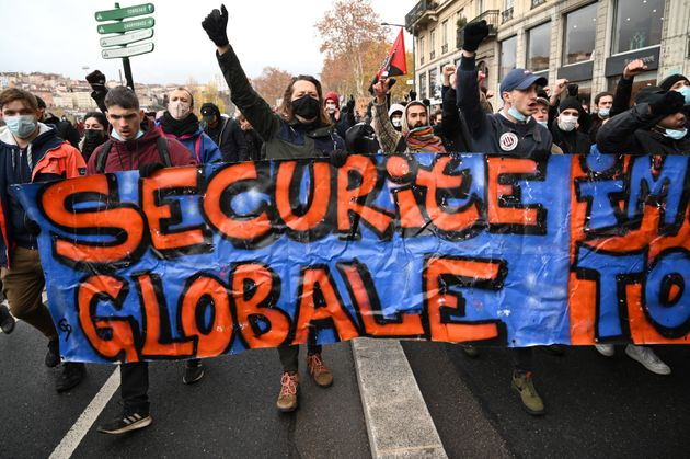 Des manifestants brandissent une banderole et lèvent leur poing en opposition à la loi Sécurité globale,...