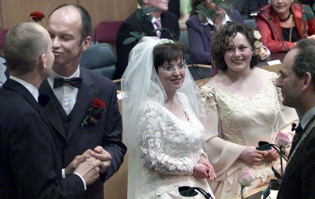 (左から)深夜のアムステルダム市役所で結婚し、キスをするドルフ・パスケルさんとゲルト・カステーさん。彼らに笑顔を向けながら、自分たちが結婚する番を待つヘレネ・ファーセンさんとアンネマリ・フースさん