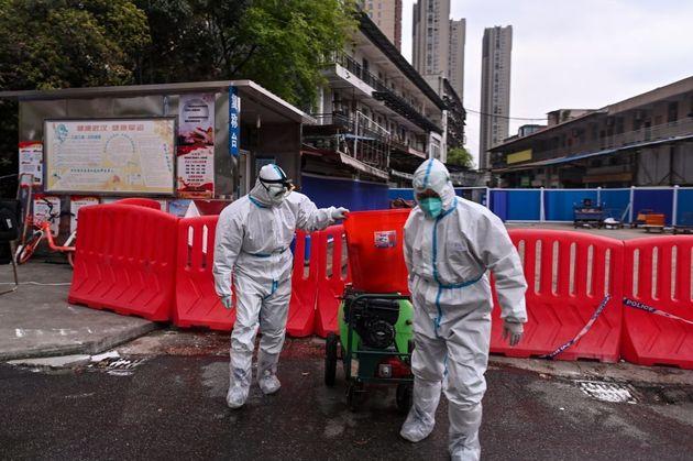 Dos trabajadores salen del mercado de Huanan, en Wuhan, cerrado en 2020 a causa del