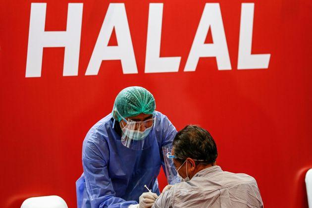 A healthcare worker inoculates a man with Sinovac's CoronaVac coronavirus disease (COVID-19) vaccine...