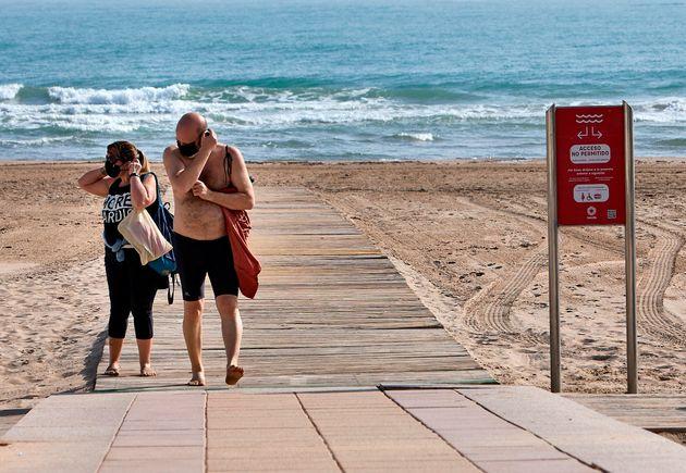 Una pareja se coloca la mascarilla en una playa de Gandía,