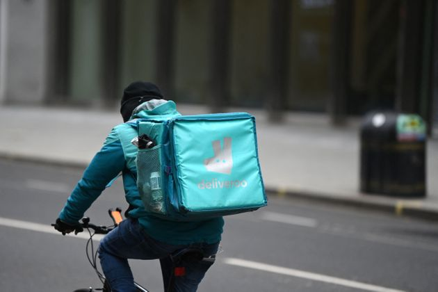 A Deliveroo rider cycles through central London on March 26, 2021. - The meal delivery platform Deliveroo...