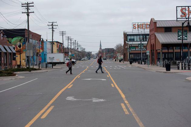 A couple walks across an empty street in the Eastern Markets in Detroit, Michigan on March, 24, 2020....