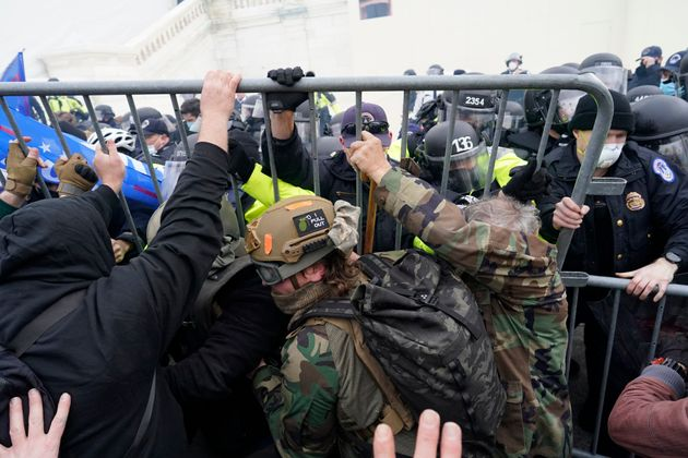 Police try to hold back protesters attempting to halt a joint session of the 117th Congress in Washington...