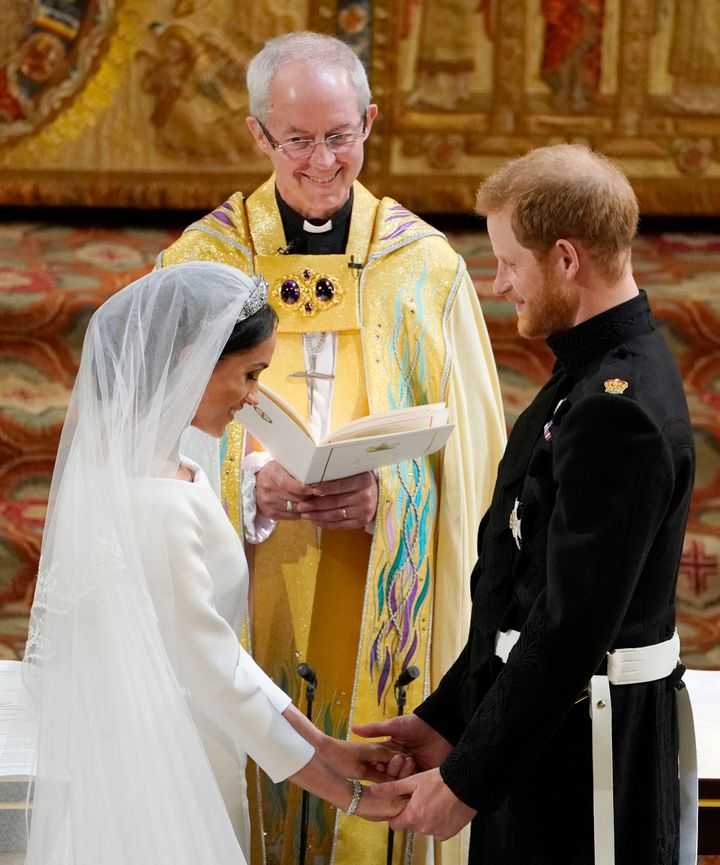 Prince Harry and Meghan Markle stand facing each other hand-in-hand before Archbishop of Canterbury Justin Welby during their
