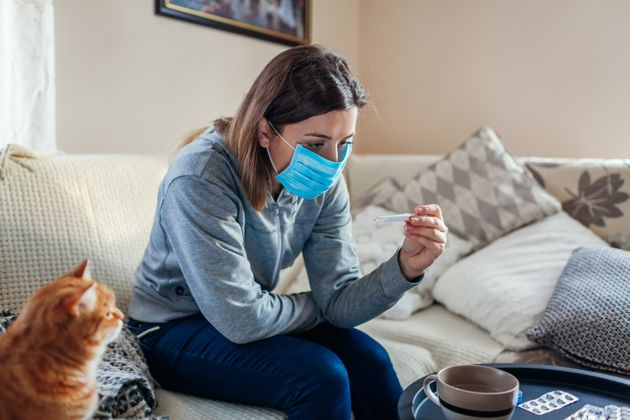 Ill infected woman checking thermometer having fever. Girl wearing protective mask while having cold,...
