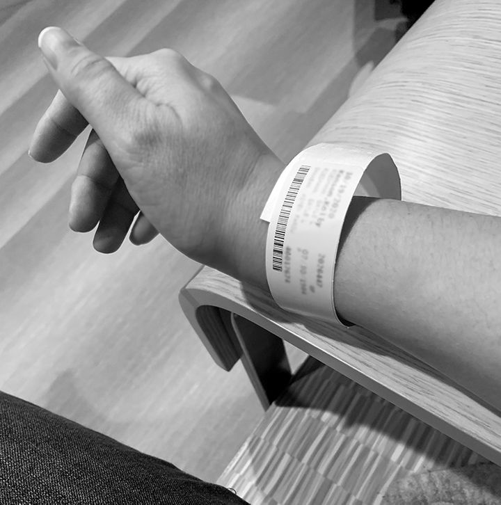 """The author staring at her wristband moments before her first MRI. She notes, """"I couldn't stop thinking that they gave me an a"""