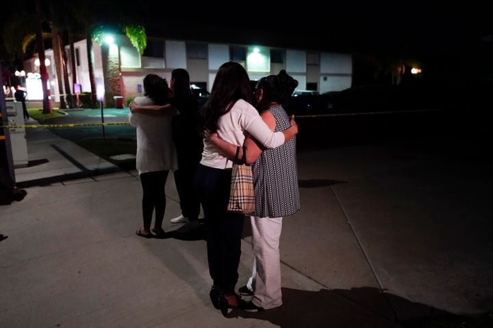 Unidentified people comfort each other as they stand near a business building where a shooting occurred in Orange, California