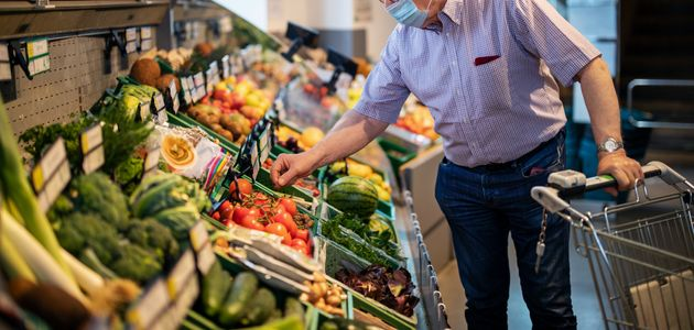 Senior man with face mask buying vegetables in a local supermarket. Elderly man doing home shopping in...