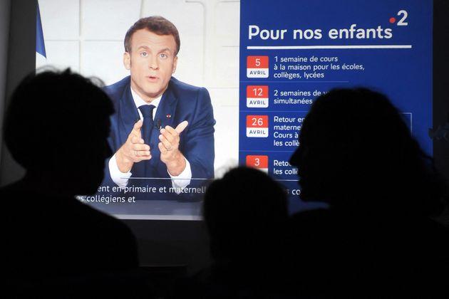 Des Français regardent l'allocution télévisée du Président Emmanuel...