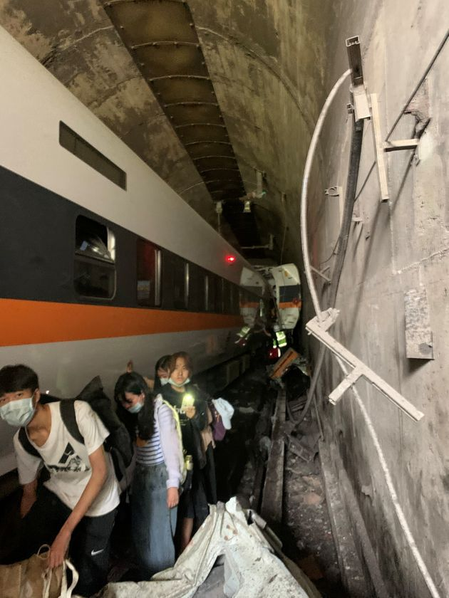 People walk next to a train which derailed in a tunnel north of