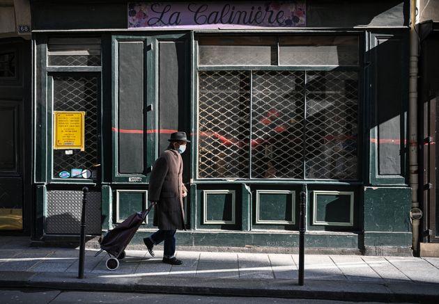 Un homme marche devant la devanture d'un magasin fermé à Paris le 20 mars