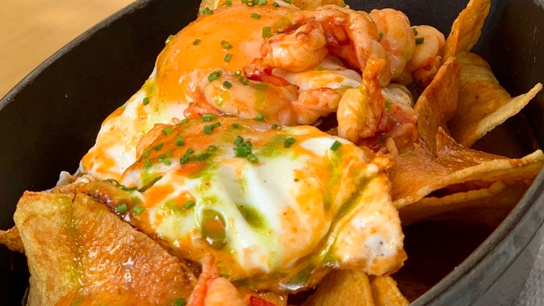 Huevos rotos con carabineros, patatas encebolladas, salsa de su propio jugo y piquillos