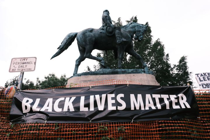 "A ""Black Lives Matter"" banner hangs before a Robert E. Lee statue in Charlottesville, Virginia. McAuliffe backed the removal"