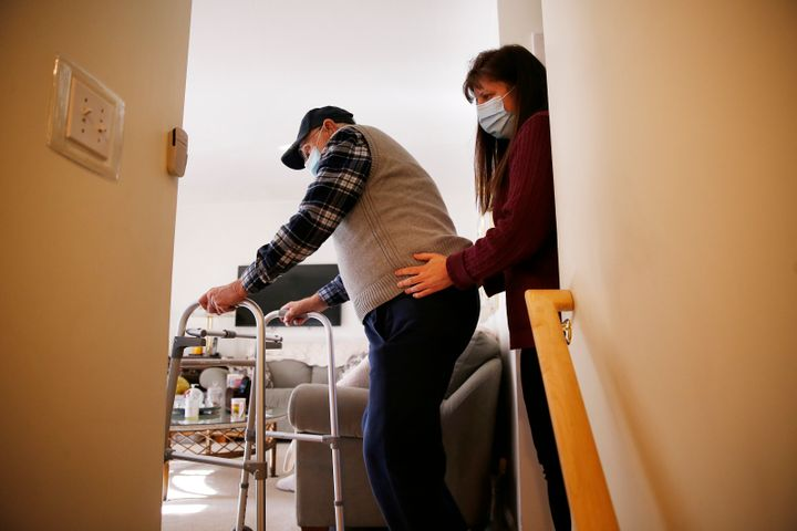A home health care aide steadies her client inside his home in Peabody, Massachusetts on Jan. 25, 2021. Ever since the 2020 p