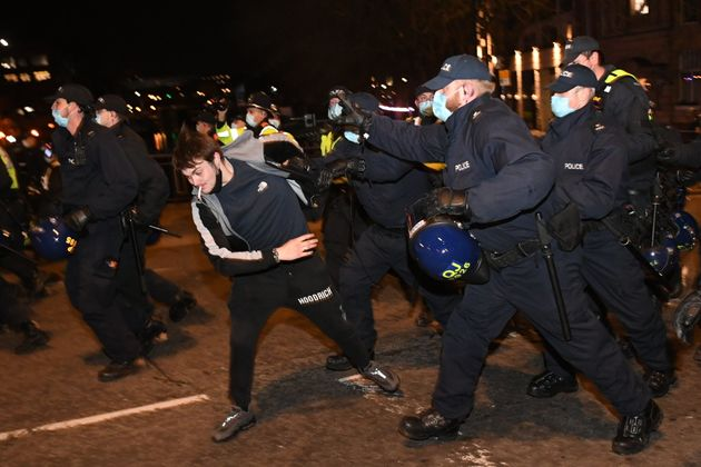 Police officers attempt to detain a man during a