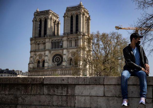 Un hombre con la mascarilla frente a la catedral de Notre Dame este domingo, en