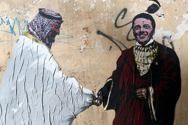Street art images depicting the former Italian prime minister Matteo Renzi (R) handshaking with Crown...