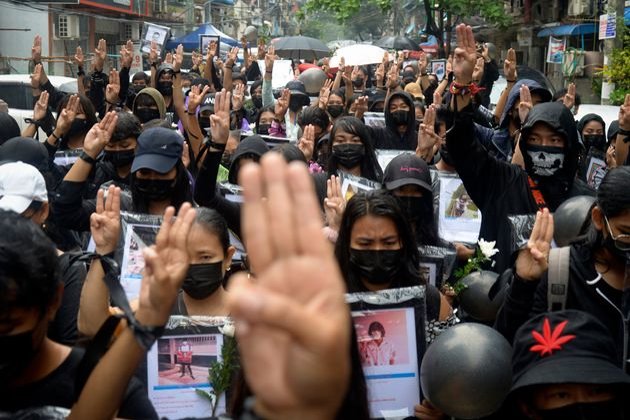 Διαδηλωτές κάνουν στο σήμα της αντίστασης με τα τρία δάχτυλα.