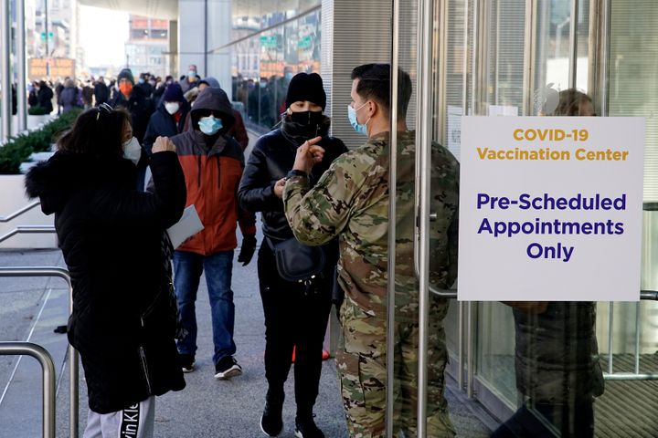 There are financial and psychological costs to getting a COVID-19 vaccine that employers can make easier — or harder — for their workers. Above, people wait to enter the Javits Center in New York City to receive a vaccine in March.