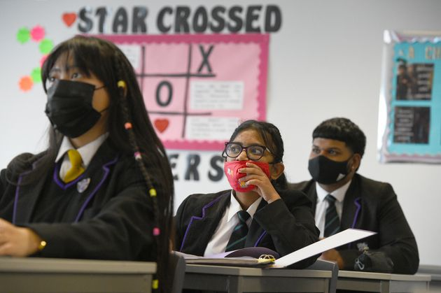 Children wearing facemasks in their Tutor Form Group listening to a virtual assembly at Hounslow Kingsley Academy in west London