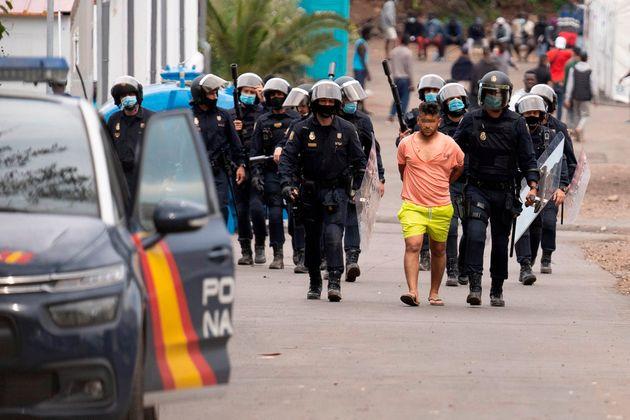 Policías antidisturbios trasladan a un detenido del campamento humanitario de Las Raíces tras los altercados...