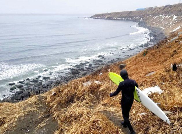 国後島の海岸で、サーフボードを抱え練習に向かうロシアの五輪代表候補=ロシアサーフィン連盟のフェイスブックから
