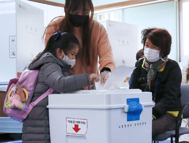 4·7 재보궐선거일인 7일 오전 울산 남구 아데라움아파트 노인정에 마련된 삼산동 제9투표소에서 한 어린이가 엄마와 함께 남구청장 재선거 투표용지를 투표함에 넣고 있다.
