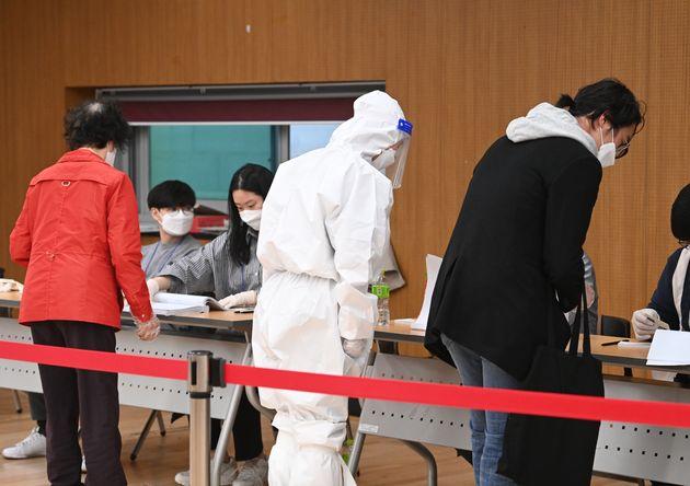 4·7재보궐 선거일인 7일 오전 서울 마포구 합정동주민센터에 마련된 투표소에서 방호복을 입은 유권자가 투표를 하기 위해 줄을 서 있다.