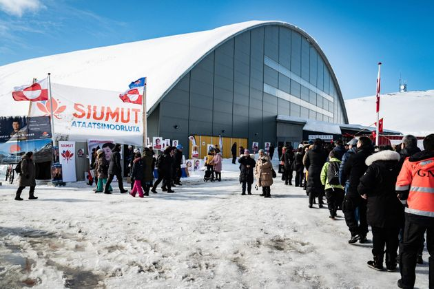 Voters stand in line to cast their ballots for the parliament election at a polling station in Greenland's...