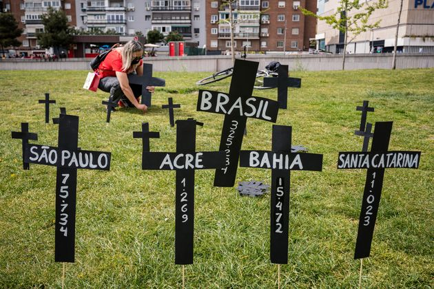 A woman lays a cross in memory of Brazil's Covid victims in the Madrid Rio park