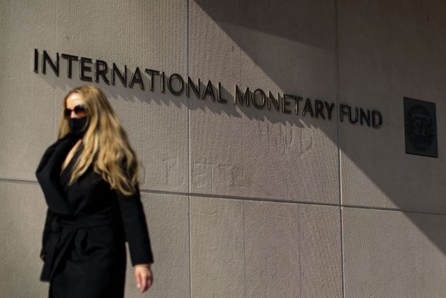 A woman walks past an International Monetary Fund headquarters(IMF) building in Washington, DC on April...