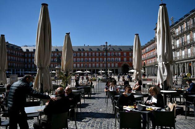 Un grupo de ciudadanos y turistas sentados en una terraza en la plaza Mayor de