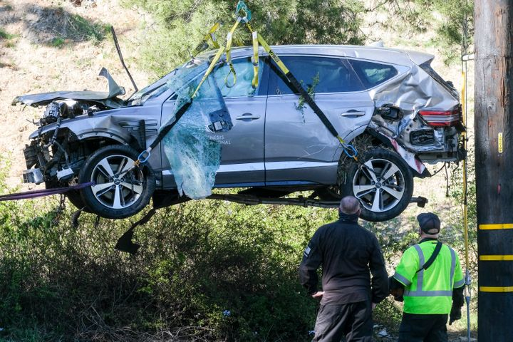 In this Feb. 23, 2021, file photo, a crane is used to lift a vehicle following a rollover accident involving golfer Tiger Woo