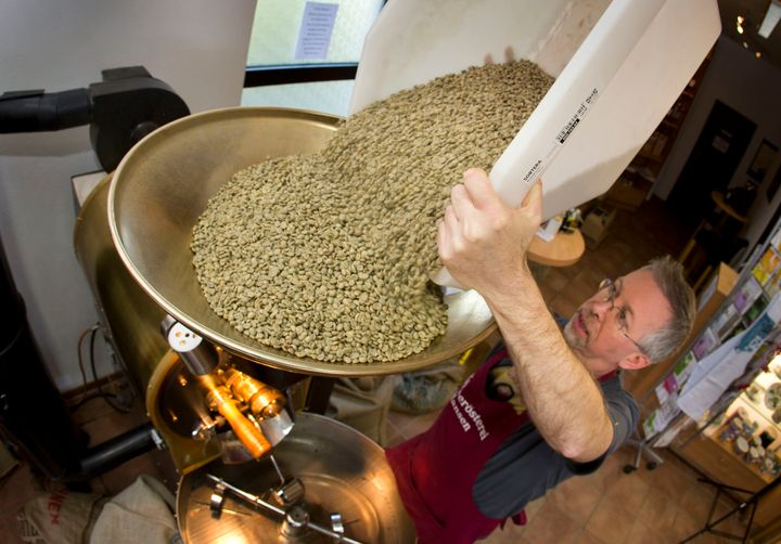 Green coffee beans (actually seeds) are poured into a roaster at Hansen Coffee Rosters in Roedermark, Germany.