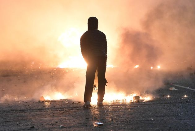 A person looks on as debris burns during clashes at the Springfield Road and Lanark Way interface in Belfast.