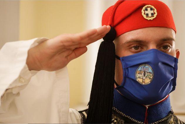 Εύζωνας, μέλος της προεδρικής φρουράς, χαιρετάει στρατιωτικά φορώντας μάσκα για προστασία από τον COVID-19....