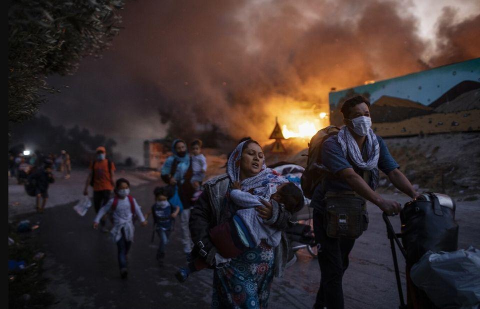 Πρόσφυγες με μάσκες προσώπου για προστασία από τον COVID-19 τρέχουν μακριά από τις φλόγες που καίνε τον...
