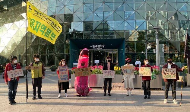 청년기후긴급행동 활동가들과 이 단체의 마스코트 김공룡이 9일 오후 5시 서울시청 앞 광장에서 기자회견을 열고 오세훈 시장의 기후위기 대응을