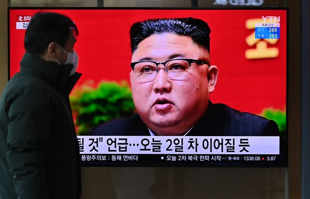 A man watches a television screen showing news footage of North Korean leader Kim Jong Un attending the...