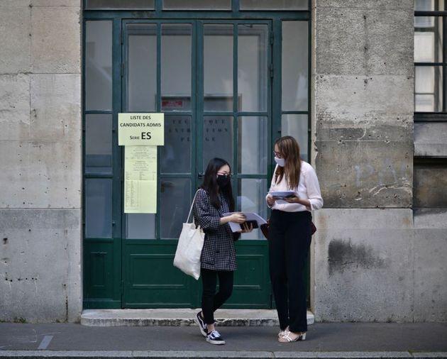 Des élèves portant des masques arrivent pour apprendre le résultat du baccalauréat au lycée Jean-de-La-Fontaine...
