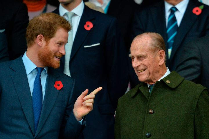 Prince Harry speaks with his grandfather Prince Philip as they watch the final match of the 2015 Rugby World Cup on Oct. 31,