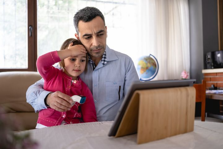 Father Talking To Family Doctor Via Video Call About His Daughter's Symptoms