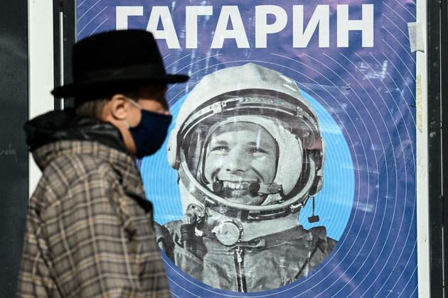A man, wearing a face mask amid the ongoing Covid-19 disease pandemic, walks past a banner with an image of Soviet cosmonaut Yuri Gagarin in Moscow on April 12, 2021. - Sixty years ago Soviet cosmonaut Yuri Gagarin became the first person in space,  marking a new chapter in the history of space exploration. (Photo by Kirill KUDRYAVTSEV / AFP) (Photo by KIRILL KUDRYAVTSEV/AFP via Getty Images)