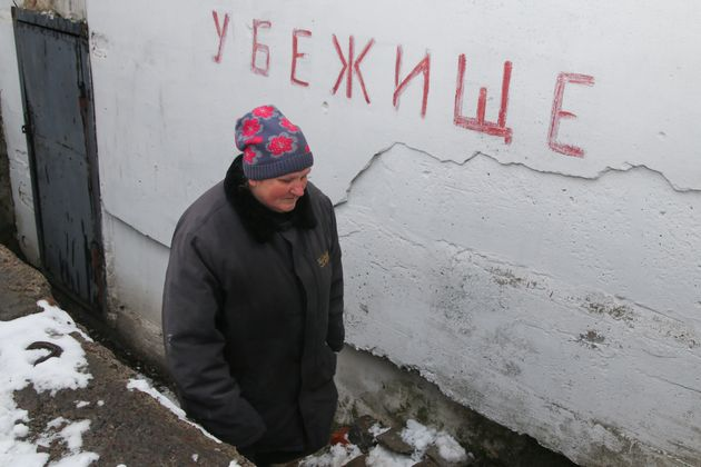 DONETSK REGION, UKRAINE - MARCH 24, 2021: A woman at the entrance to a bomb shelter in Yasinovatya (Yasynuvata)....